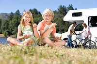 Family of four by motor home, brother and sister 8-12 eating breakfast on grass, portrait