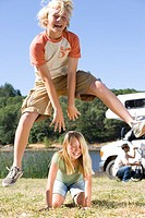 Boy 10-12 jumpping over sister 9-11 on grass by motor home