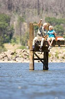 Boy 10-12 and grandfather fishing from jetty