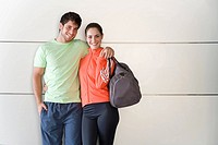 Young couple with bags in gym clothes, arm in arm, smiling, portrait