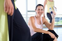 Woman with water bottle in gym studio, smiling, portrait