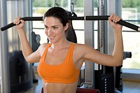 Woman using exercise equipment in gym, smiling, close-up