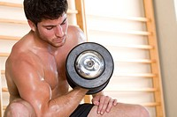 Bare chested man lifting weights in gym, low angle view