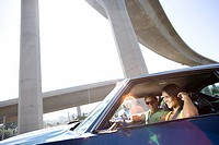 Young couple in car by freeway overpass, smiling lens flare