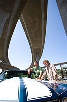 Two young men by car beneath overpass, smiling, portrait, low angle view