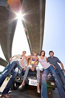 Medium group of friends on bonnet of car beneath overpass, smiling, low angle view sun flare