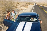 Young couple hitchhiking on desert road, in conversation with driver of car, elevated view