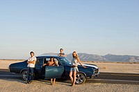 Medium group of friends by car with doors open on desert road, portrait