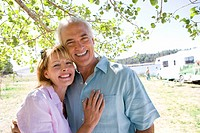 Mature couple arm in arm by motor home outdoors, smiling, portrait