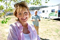 Mature woman by husband and motor home outdoors, smiling, portrait, close-up