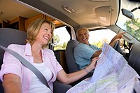 Mature woman with map in motor home by husband, smiling, low angle view