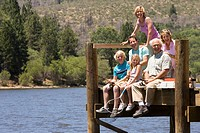 Family of three generations fishing on jetty, smiling, portrait