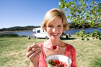 Woman with breakfast bowl by motor home and lake, smiling, portrait