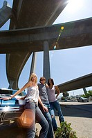 Small group of friends by car beneath overpass, portrait, low angle view lens flare