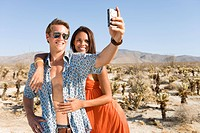 Young couple taking photograph of themselves in desert, woman embracing man, smiling