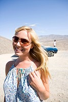 Young woman in sunglasses by car in desert, smiling, close-up