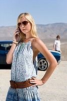 Young woman in sunglasses using mobile phone by car and man in desert