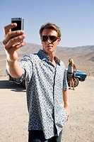 Young man in sunglasses taking photograph by woman and car in desert