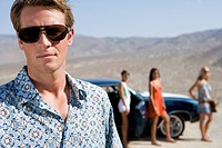 Young man in sunglasses in desert, friends by car in background