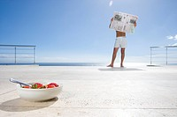 Bare chested man with face obscured by newspaper on deck by sea, bowl of strawberries in foreground lens flare