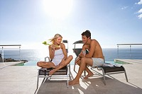 Young couple on sun beds by infinity pool and sea, man with glass smiling at woman with celery