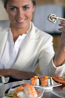 Young woman eating sushi with chopsticks, smiling, portrait differential focus