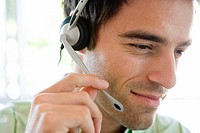 Young businessman wearing headset, smiling, close-up
