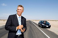 Businessman in middle of open road in desert, using electronic organiser by car