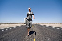 Businesswoman walking in middle of road in desert with briefcase, low angle view