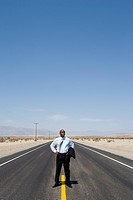 Businessman on line in middle of road in desert with hands on hips