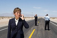 Businessmen and woman in middle of desert road using mobile phones