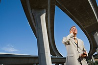 Businessman using mobile phone beneath overpasses, low angle view