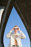 Businessman using binoculars beneath overpasses, low angle view