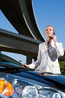 Businessman using mobile phone by car beneath overpass, low angle view