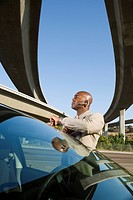 Businessman with earpiece by car beneath overpasses, low angle view