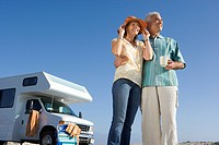 Mature couple by motor home on beach, man with mug, woman with hands on hat, low angle view