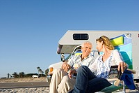 Mature couple by motor home on beach, smiling at each other, low angle view