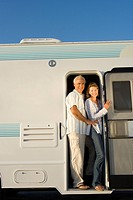 Mature couple in door of motor home, smiling, portrait