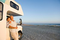 Mature woman in motor home on beach embracing husband through window, smiling, portrait