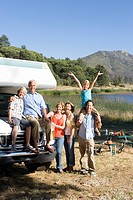 Family of three generations by motor home by lake, smiling, portrait