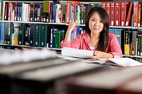 Woman studying in library, smiling, portrait