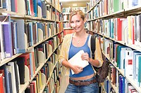Young woman with rucksack holding book in library, smiling, portrait
