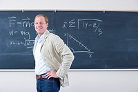 Male teacher with hands on hips by blackboard in classroom, smiling, portrait