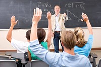 Students with arms raised in classroom, teacher by blackboard pointing to student, rear view