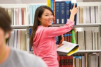 Young woman in library reaching for book, smiling