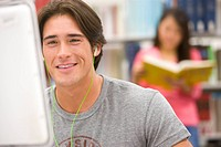Young man with earphones at computer in library, smiling, woman reading in background