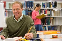 Mature man studying in library at computer, smiling
