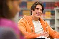 Young man studying in library, smiling, portrait