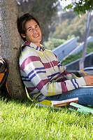 Young man leaning against tree studying, smiling, portrait