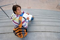 Male student with rucksack studying on steps, smiling, portrait, elevated view